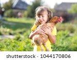 little child girl is holding... | Shutterstock . vector #1044170806
