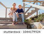 mother and son tourists sitting ... | Shutterstock . vector #1044179524