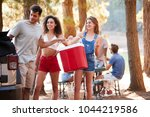 Three young adult friends with a cool box by a lake - stock photo