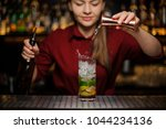 Stock photo female bartender pouring out a transparent drink from the measuring pile with splash for preparing 1044234136