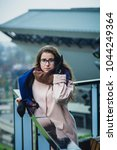 Small photo of Portrait of a beautiful brunette smiling girl in town.Pretty young model looking afar outdoor