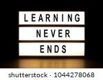 Small photo of Learning never ends light box sign board on wooden table.