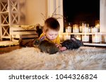 child playing with white rabbit....   Shutterstock . vector #1044326824