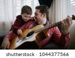 father teaching son how to play ... | Shutterstock . vector #1044377566