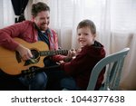 father teaching son how to play ... | Shutterstock . vector #1044377638