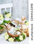 Small photo of Easter basket with eggs decorated with wreath made of carnations, buxus and catkins.