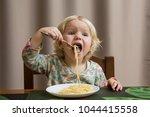 cute baby eating spaghetti... | Shutterstock . vector #1044415558