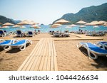 sun loungers on a beach in... | Shutterstock . vector #1044426634
