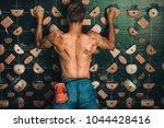 muscular man climbing wall at... | Shutterstock . vector #1044428416