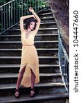Portrait of a beautiful young woman, model of fashion, in a garden stairs. - stock photo