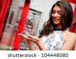 Portrait of attractive young woman buying a bracelet at a jewelry - stock photo