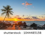 Small photo of Silhouette of a palm tree and a sand beach inside Corcovado National Park with a view over the Pacific Ocean at sunset, Osa Peninsula, Costa Rica, Central America.