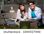 two students studying late... | Shutterstock . vector #1044527440