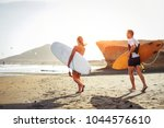 surfers couple running together ... | Shutterstock . vector #1044576610