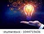 businessman holding lamp with... | Shutterstock . vector #1044715636