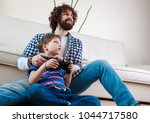 dad playing video games with... | Shutterstock . vector #1044717580