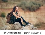 Tired Woman Sitting On A Rocky...
