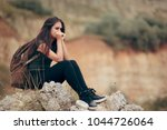 sad woman sitting on a rocky... | Shutterstock . vector #1044726064