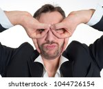 Small photo of Funny businessman with glasses made of fingers. Airplane pilot