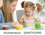 kid girl and mom paint together ... | Shutterstock . vector #1044741940