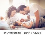 happy smiling family in bed. | Shutterstock . vector #1044773296