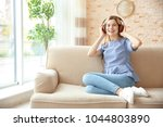 young woman listening to music... | Shutterstock . vector #1044803890