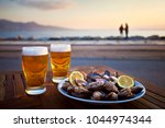 beer and mussel at the sunset   Shutterstock . vector #1044974344