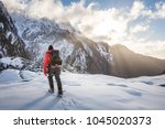 a guide traverses glacial ice... | Shutterstock . vector #1045020373