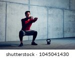 athletic man doing squats... | Shutterstock . vector #1045041430