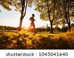 man running in park during... | Shutterstock . vector #1045041640