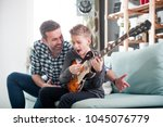 son and father playing electric ... | Shutterstock . vector #1045076779