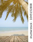 Small photo of Empty wooden terrace over tropical island beach with coconut palm at summer time