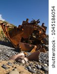 Small photo of Withered, half buried in the sand beach, propeller in a low perspective at the stern of a wrecked pusher boat. Focus on propeller. Clear blue sky. Vila Nova de Milfontes, Portugal.