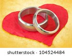 wedding rings on the red crumpled paper heart - stock photo