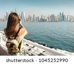 Dubai travel tourist woman on vacation in the Palm Jumeirah taking photo on the camera.