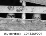 Small photo of Two homeless illegal refugess girls in abroad sheltter portrait. Social problems concept. Woman slavery. Pitiful female eyes begging for help. Kidnapped sisters in locked up hidden room funny concept