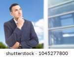 Small photo of Smart visionary businessman looking up on glass building background as successful entrepreneur concept