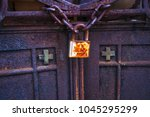 old rusty lock on the gates of... | Shutterstock . vector #1045295299