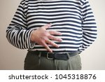 man with hand on belly   Shutterstock . vector #1045318876