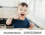 beautiful cute baby eats rice... | Shutterstock . vector #1045320604