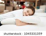nice little girl hugs pillow in ... | Shutterstock . vector #1045331359
