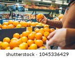 man choose oranges from shelf... | Shutterstock . vector #1045336429