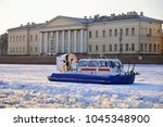 Small photo of ST.PETERSBURG, RUSSIA - MARCH 07, 2018: The boat is MOE from ice blocks against the building of the Academy of Sciences on the University embankment at sunset in Saint-Petersburg