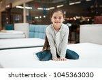 happy little girl sitting on... | Shutterstock . vector #1045363030