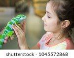 pretty little girl with iguana... | Shutterstock . vector #1045572868