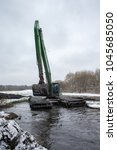 Small photo of Balashikha, Moscow area, Russia - January 05, 2017: The excavator cleans the Pekhorka river bed from silt and threaten.