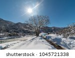 Small photo of Giant tree covered snow and tourists crossing the Deai-bashi suspension bridge to the village in winter in Shirakawa-go,Ono ,Gifu,Japan.