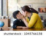 asian mother kissing her son ... | Shutterstock . vector #1045766158