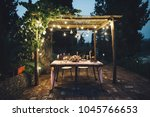 Decorated outdoor wedding table with flowers, lights and candles in rustic style - stock photo