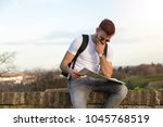 young teenager is siting  on... | Shutterstock . vector #1045768519